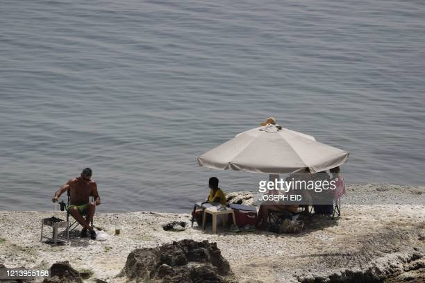 People gather beneath an umbrella along a beach in Amchit in northern Lebanon on May 19 despite beaches being legally closed due to COVID-19...