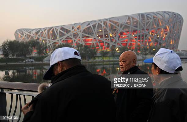 People gather beside a railing for a view of the Bird's Nest stadium in Beijing on November 4 2009 More than a year after the Beijing Olympics the...