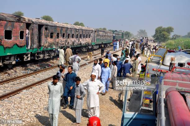 People gather beside the burntout train carriages after a passenger train caught on fire near Rahim Yar Khan in Punjab province on October 31 2019 At...