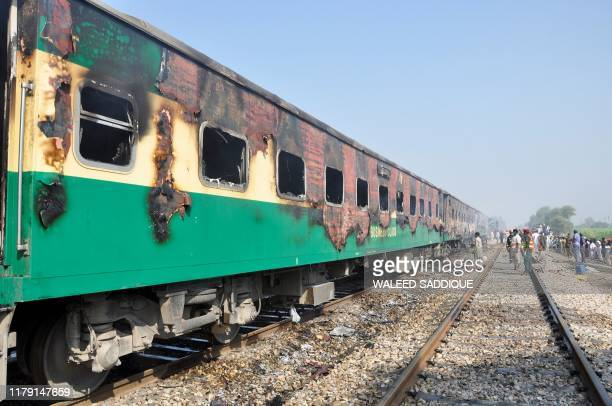TOPSHOT People gather beside the burntout train carriages after a passenger train caught on fire near Rahim Yar Khan in Punjab province on October 31...