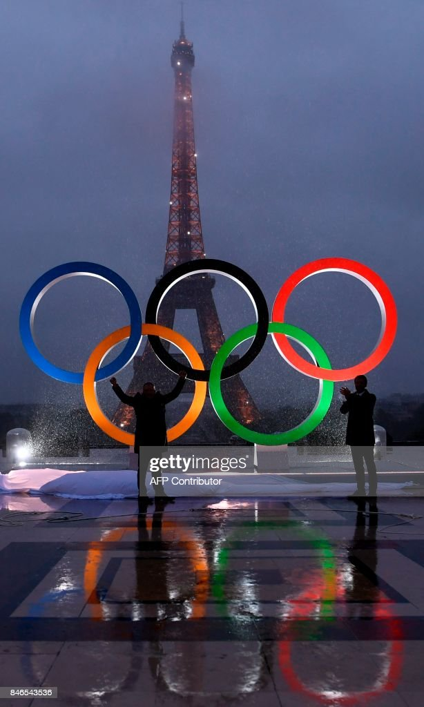 People gather beside The Olympics Rings as they are reflected in rainwater on the Trocadero Esplanade near the Eiffel Tower in Paris, on September 13, 2017, after the International Olympic Committee named Paris host city of the 2024 Summer Olympic Games. The International Olympic Committee named Paris and Los Angeles as hosts for the 2024 and 2028 Olympics on September 13, 2017, crowning two cities at the same time in a historic first for the embattled sports body. /