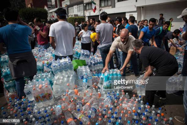 People gather bottles of water to share out among rescue brigades and affected people a day after the magnitude 71 earthquake jolted central Mexico...