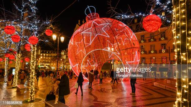 People gather by a giant Christmas decoration in Praca Luís de Camões on December 11, 2019 in Lisbon, Portugal. The city shows every year a variety...