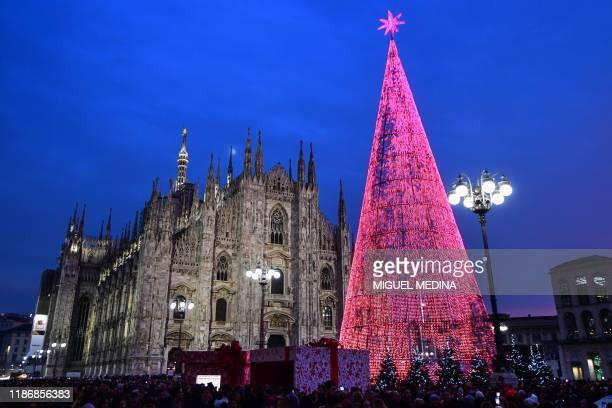 People gather by a giant Christmas tree on Piazza del Duomo in Milan on December 7, 2019.