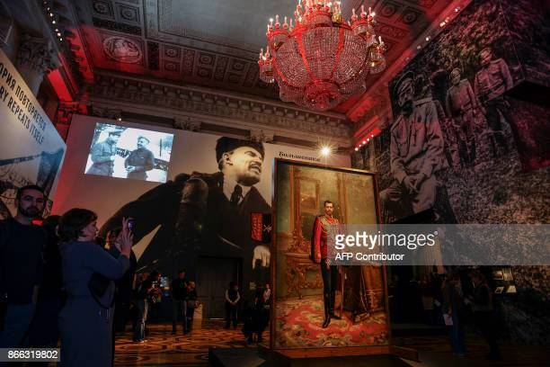 People gather by a portrait of the last Russian tsar Nicholas II and a huge image of the Soviet Union founder Vladimir Lenin during the opening of...
