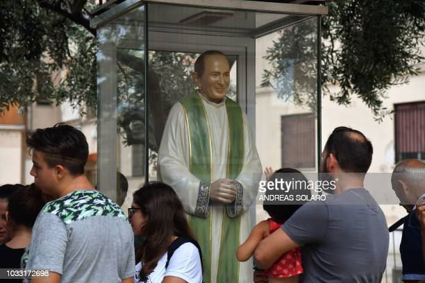 People gather by a statue of late priest Pino Puglisi outside the house museum and Padre Nostro welcome center in the Brancaccio district of Palermo...