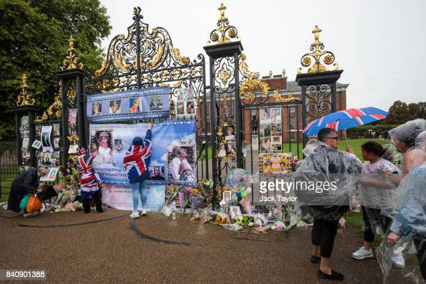 People gather by flowers photographs and tributes around an entrance gate to Kensington Palace ahead of the 20th anniversary of the death of Diana...