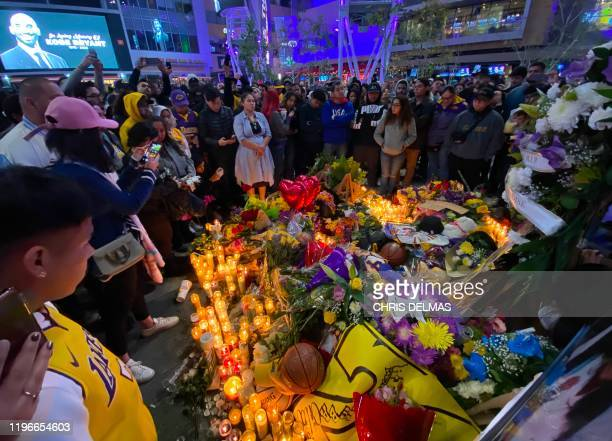 People gather by the Staples Center in Los Angeles on January 26 2020 as they pay tribute to former NBA and Los Angeles Lakers player Kobe Bryant...