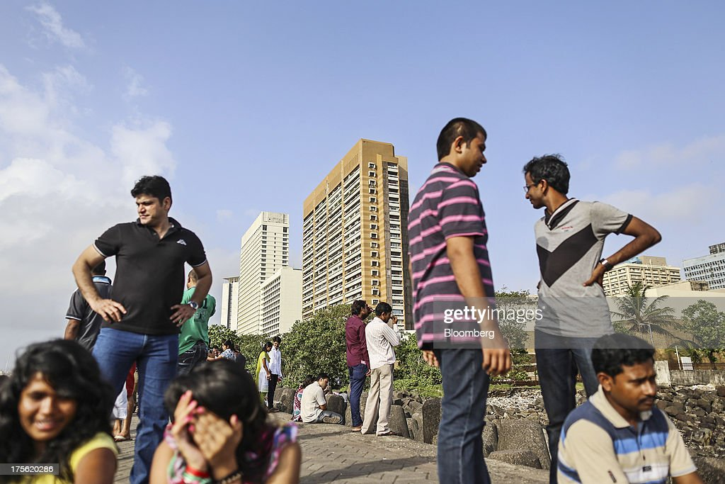 People gather by the waterfront as residential and commercial buildings stand in the Nariman Point area of Mumbai, India, on Sunday, Aug. 4, 2013. India's purchasing managers index (PMI) for services figures for July are scheduled for release on Aug. 5. Photographer: Dhiraj Singh/Bloomberg via Getty Images