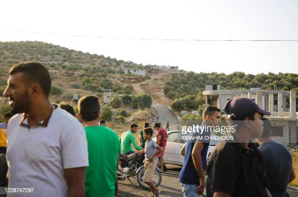 People gather downhill from a house where suspected members of the Islamic State group were hiding before a raid by Lebanese police intelligence, in...