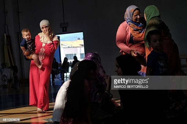People gather during a celebration of Eid alFitr marking the end of the fasting month of Ramadan in a gymnasium in Saluzzo near Turin on July 17 2015...