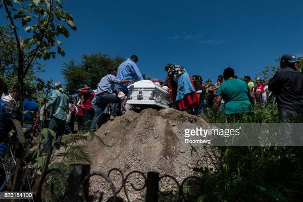 People gather during a funeral procession for one of the nine people who died in a clash between rival gangs of huachicoleros in the town of...