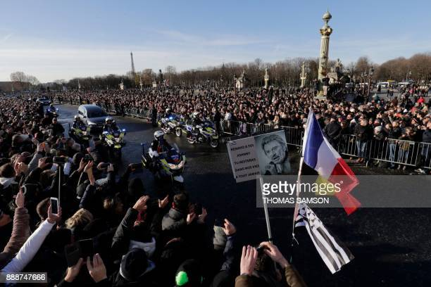 TOPSHOT People gather during a 'popular homage' to late French singer Johnny Hallyday as his coffin is driven down the Concorde square on December 9...