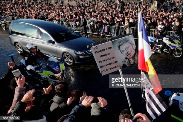 People gather during a 'popular homage' to late French singer Johnny Hallyday as his coffin is driven down the Concorde square on December 9 2017 in...