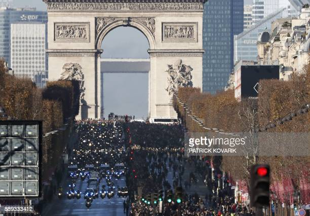 People gather during a 'popular homage' to late French singer Johnny Hallyday as his coffin is driven down the ChampsElysees avenue on December 9...