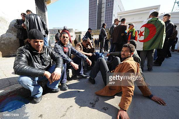 People gather during a protest against unemployment as policemen stand guard on February 6 2011 in front of the Ministry of Labour in Algiers...