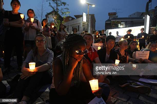 People gather during a vigil in downtown Seoul to remember victims of the shooting at an Orlando nightclub on June 13, 2016 in Seoul, South Korea. An...