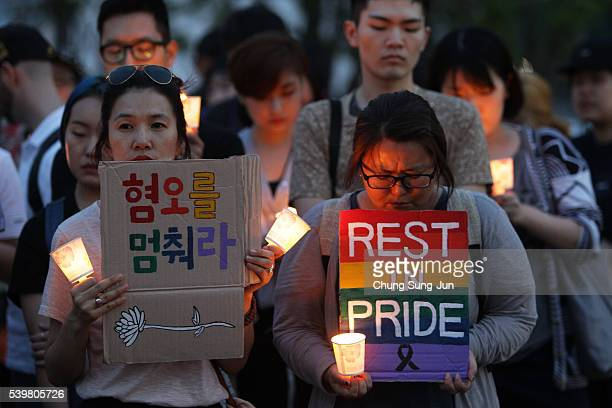 People gather during a vigil in downtown Seoul to remember victims of the shooting at an Orlando nightclub on June 13 2016 in Seoul South Korea An...