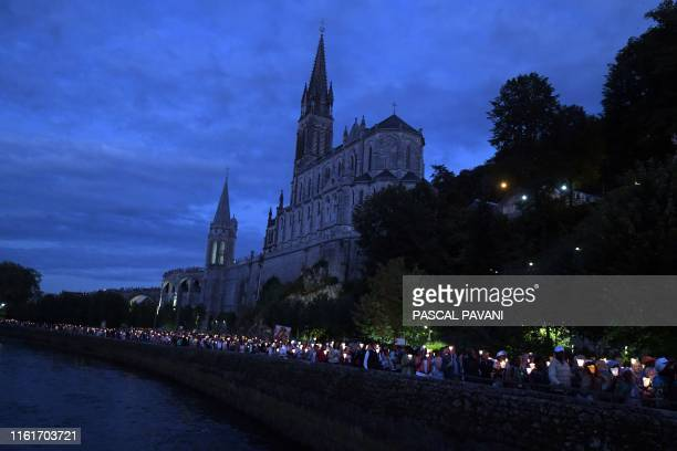People gather during the Marian procession in the shrine of Our Lady of Lourdes during the annual Catholic pilgrimage of Lourdes on August 14 2019