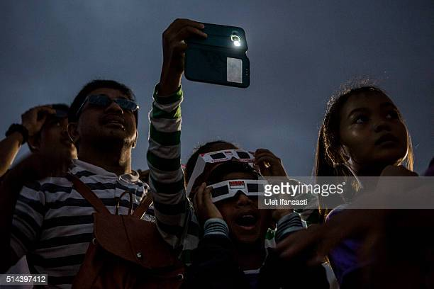People gather during total solar eclipse in Palembang city on March 9 2016 in Palembang South Sumatra province Indonesia A total solar eclipse swept...
