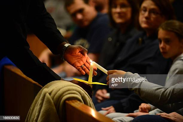 People gather for a candlelight vigil at St Mary's Catholic Church in West Texas on April 18 in memory of those who lost their lives in the massive...