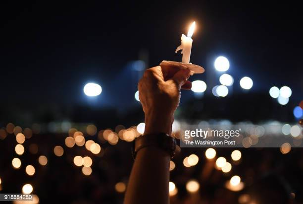 People gather for a candlelight vigil in honor of the victims of the Marjory Stoneman Douglas High School shooting on Thursday February 15 2018 in...