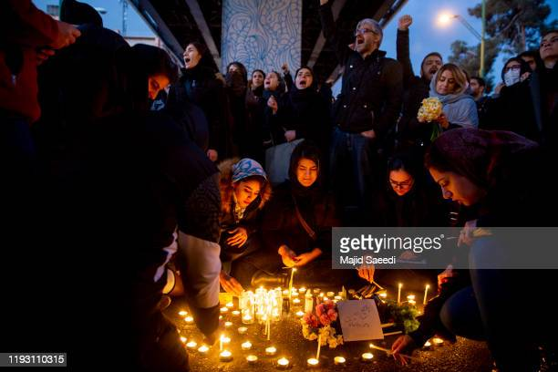 People gather for a candlelight vigil to remember the victims of the Ukraine plane crash, at the gate of Amri Kabir University where some of the...