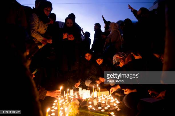 People gather for a candlelight vigil to remember the victims of the Ukraine plane crash at the gate of Amri Kabir University where some of the...