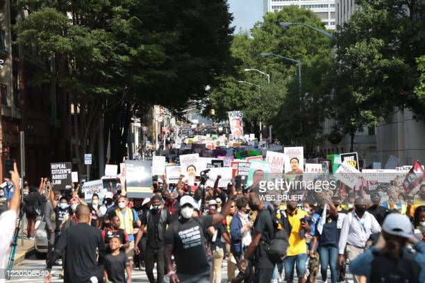 TOPSHOT People gather for a civil rights National Association for the Advancement of Colored People protest march on June 15 2020 in Atlanta Georgia...
