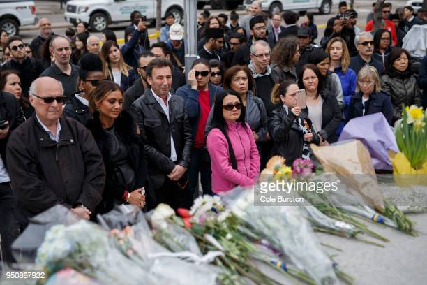 People gather for a moment of silence at a memorial for victims of the mass killing on Yonge St at Finch Ave on April 24 2018 in Toronto Canada A...