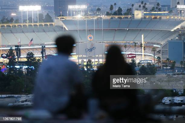 People gather for a picnic on a hillside overlooking Dodger Stadium during a game between the Colorado Rockies and the Los Angeles Dodgers on August...
