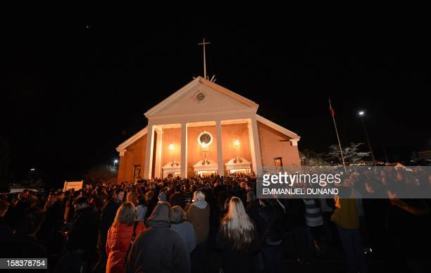 People gather for a prayer vigil at St Rose Church following an elementary school shooting in Newtown Connecticut December 14 2012 A young gunman...