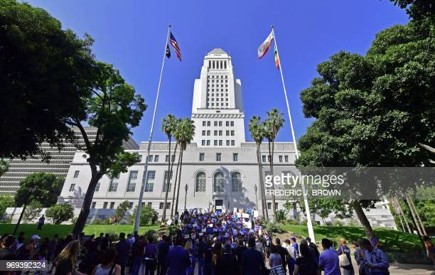 People gather for a rally organized by local families their supporters and civil rights organizations on the steps of City Hall in Los Angeles...