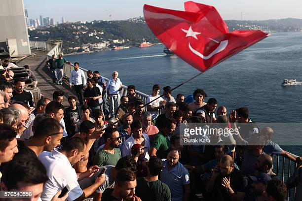 People gather for celebration around Turkish police officers loyal to the government standing atop tanks abandoned by Turkish army officers against a...