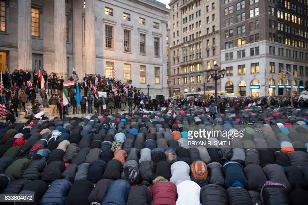 TOPSHOT People gather for evening prayer at a rally at Brooklyn Borough Hall as Yemeni bodega and grocerystores shut down to protest US President...