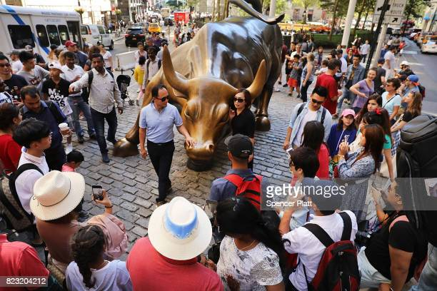 People gather for pictures around Charging Bull which is often referred to as the Wall Street Bull on July 26 2017 in New York City The Dow Jones...