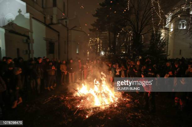 People gather for the annual bonfire outside the Saint Sava church during the ceremonial burning of dried oak branches symbolising the Yule log...