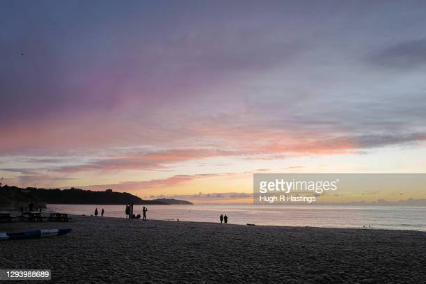 People gather for the first sunrise of the year at Gyllyngvase Beach on January 1, 2021 in Falmouth, United Kingdom. January 1st 2021 marks the first...