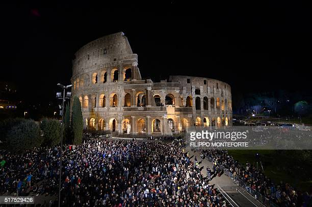 People gather for the Via Crucis torchlight procession on Good Friday at the Colosseum on March 25 2016 in Rome Christians around the world are...