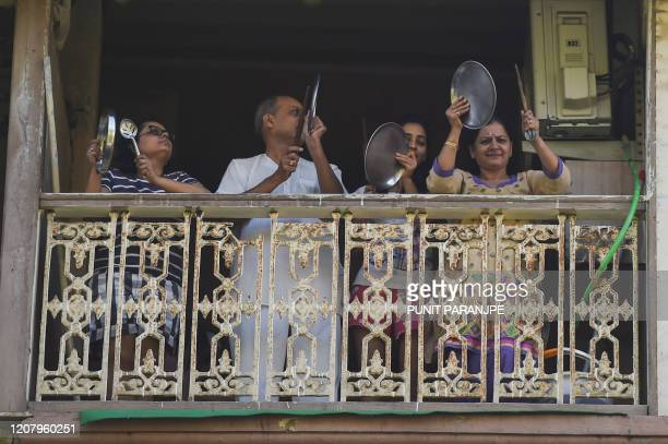 People gather in a balcony of a residential building to clap and make noise with kitchenware to thank essential service providers during a oneday...