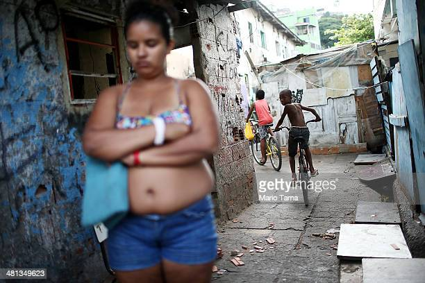 People gather in an impoverished section of the unpacified Complexo da Mare slum complex one of the largest 'favela' complexes in Rio on March 29...