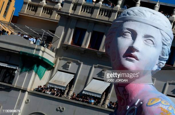 People gather in balconies around a 'falla' to watch the traditional 'Mascleta' during the Fallas festival in Valencia on March 16 2019