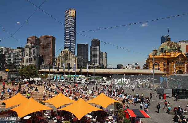 People gather in Federation Square to watch the Dame Elisabeth Murdoch public memorial on large screens as it is held across the road at St Paul's...