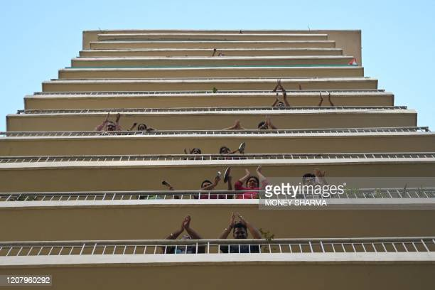 TOPSHOT People gather in flat balconies of a residential building to clap and make noise with kitchenware to thank essential service providers during...