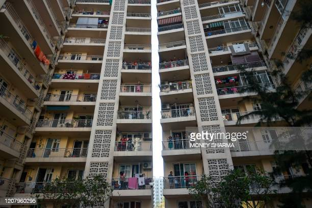 People gather in flat balconies of a residential building to clap and make noise with kitchenware to thank essential service providers during a...