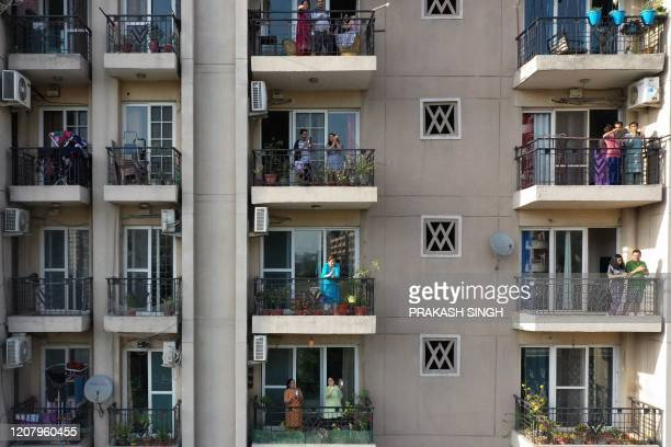 TOPSHOT People gather in flat balconies of a residential building to clap to thank essential service providers during a oneday Janata curfew imposed...