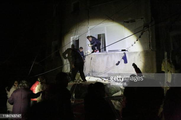 People gather in front of a damaged building in the coastal city of Durres, west of capital Tirana, after an earthquake hit Albania, on November 26,...