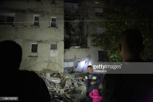 People gather in front of a damaged building in the coastal city of Durres west of capital Tirana after an earthquake hit Albania on November 26 2019...