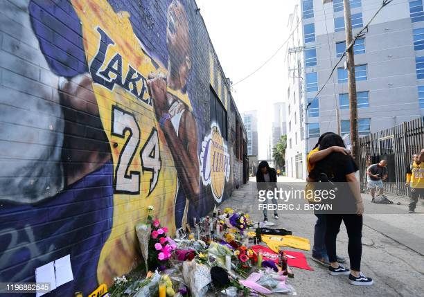 People gather in front of a Kobe Bryant mural in downtown Los Angeles on January 27 2020 Nine people were killed in the helicopter crash which...