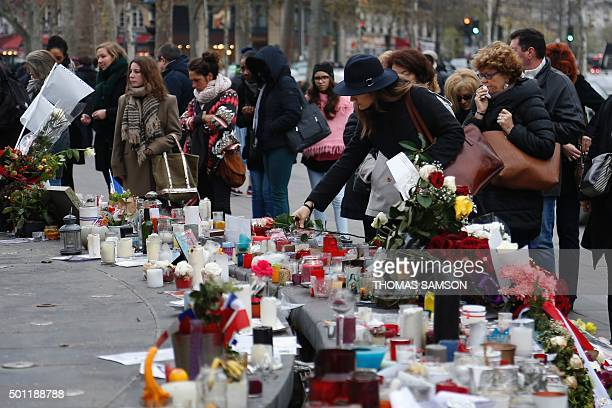People gather in front of a makeshift memorial in Place de la Republique square in Paris on December 13 a month after the Paris terror attacks on...